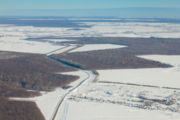 aerial view over snowy field and road