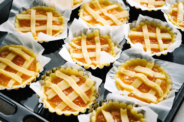 Preparing pies with pastry and jam