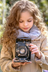 Little girl with old retro photography camera in hands outdoors