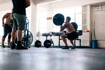 Bodybuilder exercising with heavy weights at crossfit gym