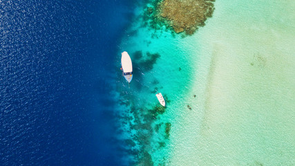 Beautiful coral reef with anchoring boats