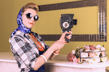 Photo of beautiful girl in retro style pin-up with a vintage camera in hand