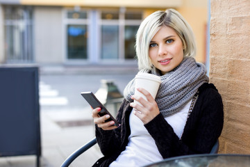 Woman With Mobile Phone And Coffee Cup At Sidewalk Cafe
