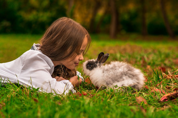 Happy little child girl with cute rabbit. Portrait of kid  with pet. Easter.