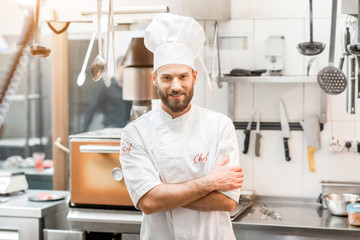 Portrait of chef cook in uniform at the restaurant kitchen