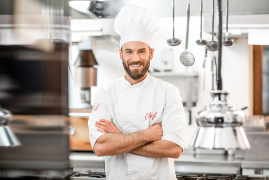Portrait of handsome positive chef cook at the restaurant kitchen