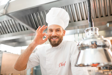 Portrait of a handsome chef cook in uniform showing delicious sign at the restaurant kitchen