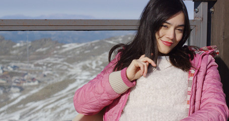 Beautiful asian girl enjoys sunny winter weather on the mountain terrace. She has marvelous view behind her back. Smiling to the camera.
