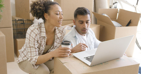 Young mixed race couple sitting on the floor of new home they just moved in. They using laptop for planning.
