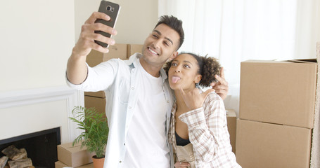 Fun young couple taking their selfie on a mobile phone pulling faces as they pose in front of packing boxes in their new home
