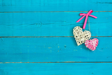 Two hearts hanging by pink ribbon on antique teal blue wood door; wooden background with painted copy space