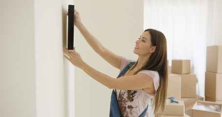 Attractive young woman trying out a placement for a picture on a wall in her new home during a DIY renovation project