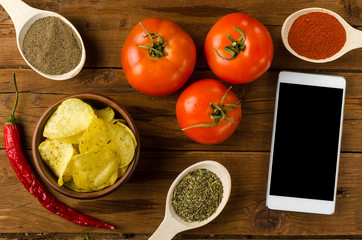 Potato chips in a bowl on a wooden table, tomatoes and smartphon