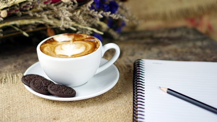 Cappuccino coffee and sweet chocolate brownies cake. A cup of latte, cappuccino or espresso coffee with milk put on a wood table with dark roasting coffee beans. and memo notebook.