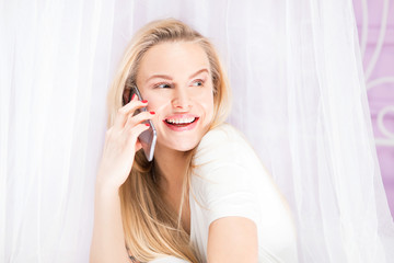 Young blonde girl talking by phone.