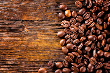 Macro image of roasted coffee beans at brown textured wooden boa