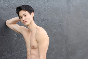 Shirtless man with a perfect body leaning on a wall