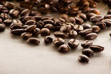 Kaffeebohnen und Kaffeetasse auf weißem Leinen mit Löffel und Jutesack