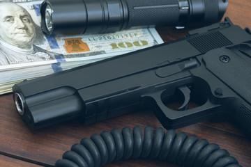 money, tactical flashlight and a weapon - safety concept