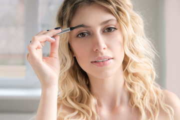 Young blonde woman shaping her eyebrow
