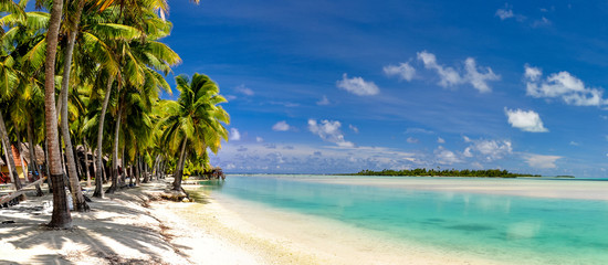 Stunning wide angle view of a beautiful beach on the remote island of Aitutaki, north of the main island Rarotonga, Cook Islands. White sand beach, shallow water, palm trees and a bungalow resort. Wall mural