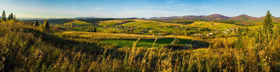 Village and autumn forest in mountains panorama.