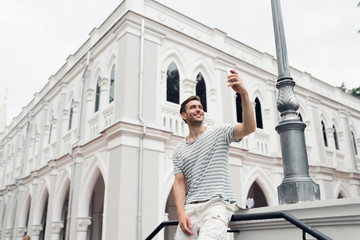 Young handsome man  taking a picture on his mobile phone  while touring a foreign city