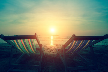 A couple of deck chairs at dusk on sea beach.