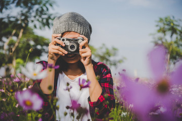 Hipster girl with vintage camera focus shooting flowers at park.