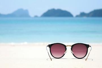 Fashion sunglasses on sea beach under clear blue sky. Summer hol Wall mural