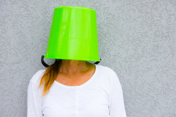 Woman with bucket over head hiding