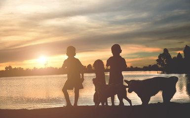A silhouette of a happy family of four people, baby, and child, and their dog in front of a sunsetting sky, with room four copy space or text