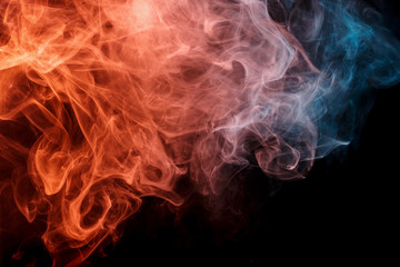 Abstract smoke Weipa. Personal vaporizers fragrant steam. The concept of alternative non-nicotine smoking. Orange turquise smoke on black background. E-cigarette. Evaporator. Taking Close-up. Vaping.