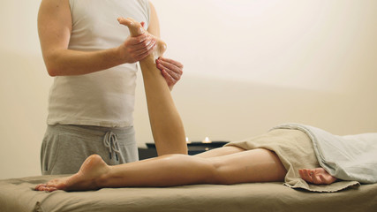 Oil sesame legs massage for young woman - cosmetic and healthcare concept