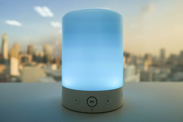 close up blue light wireless music speaker on white table