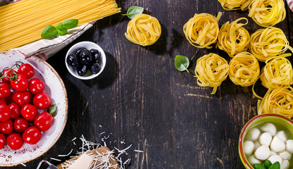 Italian food ingredients for cooking on a wooden background.