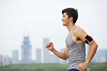 young asian man running in park against skyscrapers in the background