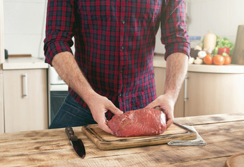 Man holding of fresh piece of beef on wooden table