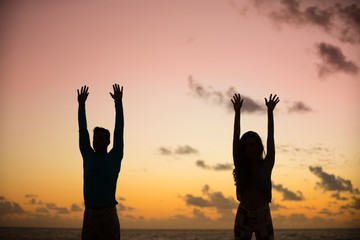 Silhouette of young couple doing yoga relaxation exercises on the beach by the sea at sunrise .
