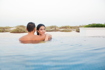 Expat couple embracing in swimming pool.