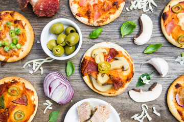 Top View of Different Types of Small Pizza with Ingredients on Wooden Background