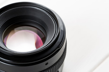 Close-up shot of photo lens on a white wooden table