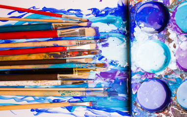 Paints, brushes and palette on the white background. The workplace of the artist. Banner for school