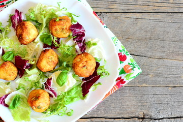 Golden fried potato balls with pumpkin seeds served with lettuce mix and basil on a plate. Vintage wooden background with copy space for text. Easy and tasty potato recipe. Top view