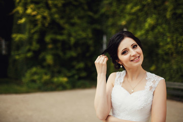 smiling bride holding a lock of his hair