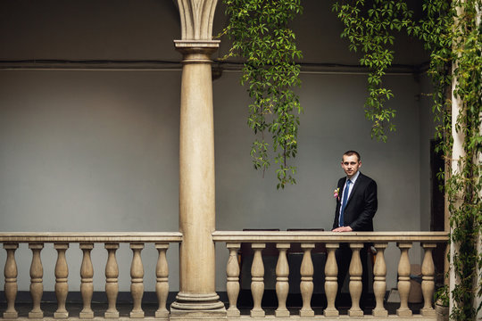 serious elegant groom on the balcony
