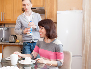 Man and woman eating in   kitchen.
