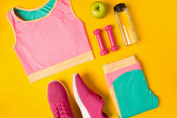 Fitness accessories on yellow background. Sneakers, bottle of water, dumbbells and sport top.