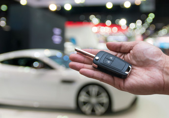 Man hand holding and giving a car key remote on photo blurred of