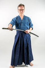 Adult caucasian male with glasses training Iaido drawing a Japanese sword with focused look. Studio shot with white background.